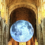 Glowing pale blue and grey, Luke Jerram's huge moon artwork hangs in golden light in the nave of a vast cathedral.