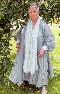 Chloë stands in the greenery of an apple tree. She wears a long flowing coat and scarf in soft colours. Her hair is silver and spiky short.